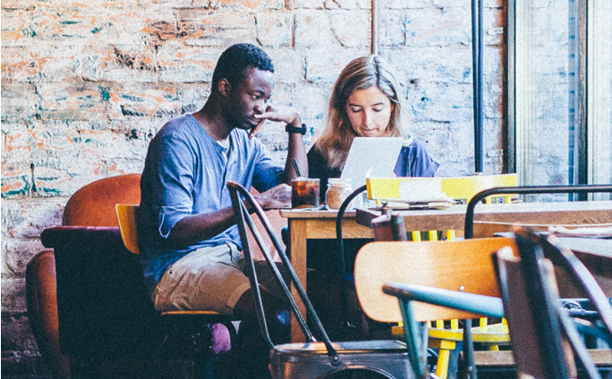 Woman and man sitting at a coffee shop doing their work