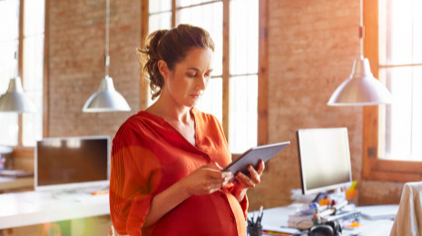 pregnant woman looking at tablet